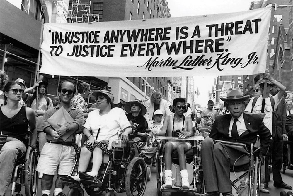 "Image: black and white photograph of individuals in wheelchairs, and with other visible disabilities, taking part in a political march. Participants carry a banner that reads: ""Injustice Anywhere Is a Threat To Justice Everywhere ~ Martin Luther King Jr."""