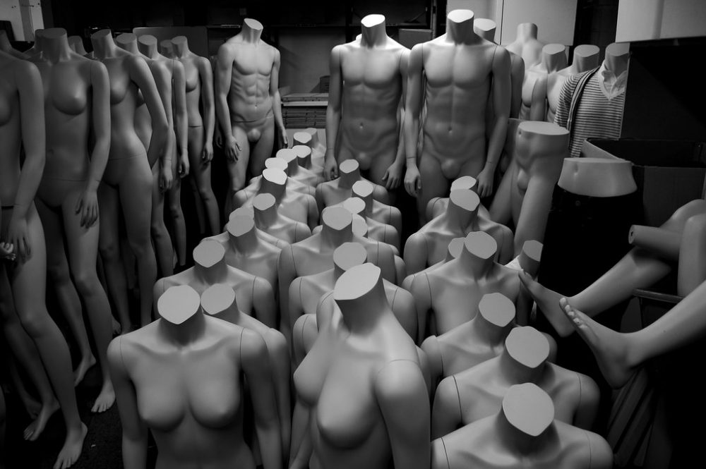 Image: male and female headless mannequins in a storeroom