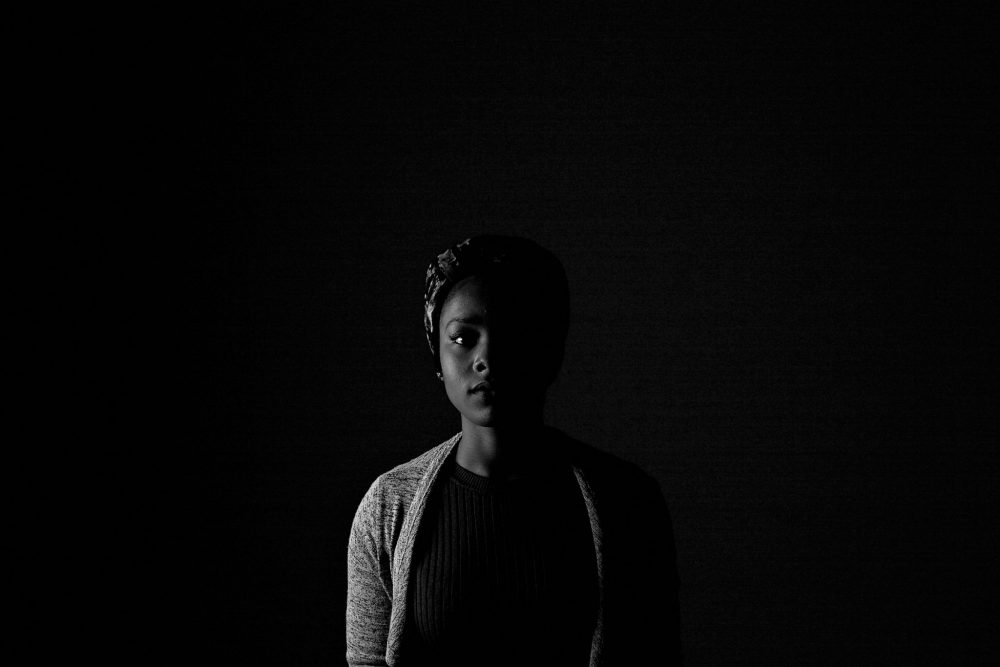 Image: a young African woman standing in darkness