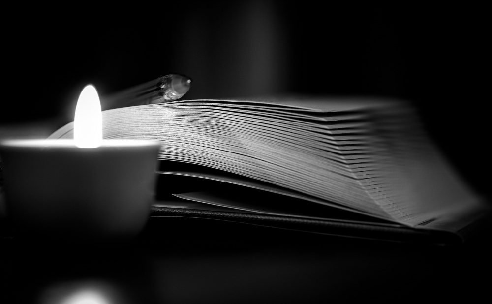 image: a candle, writing book and pen