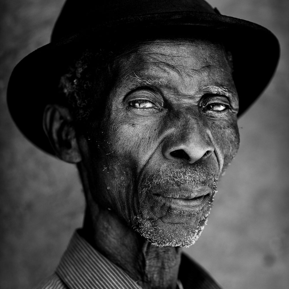 A close up of an African man wearing a hat